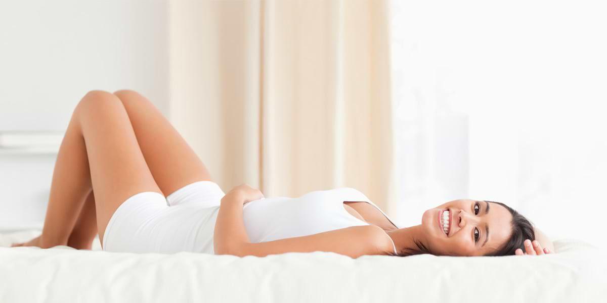 Frau auf dem Bett mit glatten Beinen